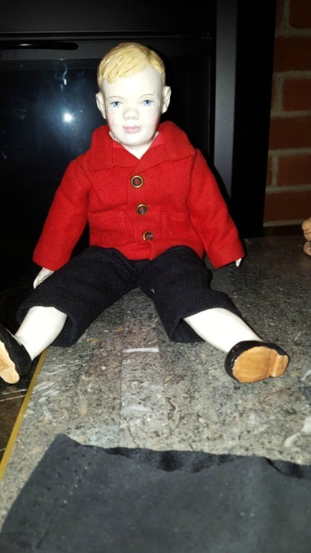 male doll wearing red coat and black pants