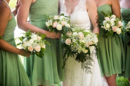 bridesmaids in green dresses standing next to bride