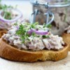 Creamed tuna on slices of toast garnished with herbs and red onion