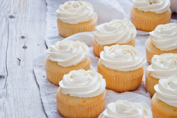 Several vanilla cupcakes with white frosting