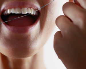 Close up of woman's teeth being flossed