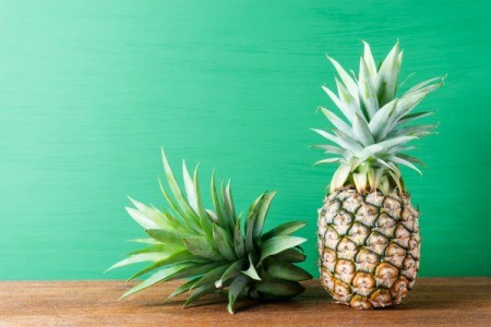 Pineapple and top of pineapple against green background