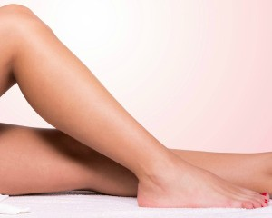 Smooth women's lower legs against peach background