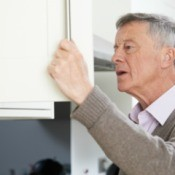 Elderly man looking in cupboard with perplexed expression