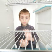 Young boy looking into empty fridge with sad expression