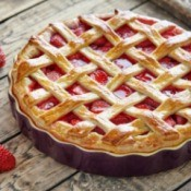 A baked strawberry pie and loose strawberries on wooden table