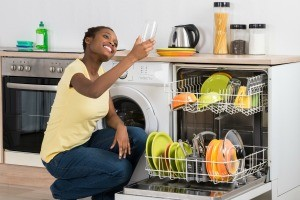 Woman smiling as she looks at a glass while she empties dishwasher