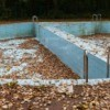 Abandoned empty outdoor swimming pool filled with leaves