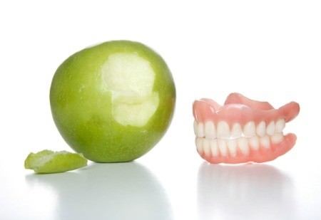Apple with a bite next to it sitting next to a pair of dentures