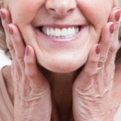 Close up of the mouth of a smiling senior woman with her hands on either side of her jaw
