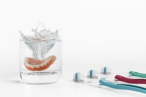 Dentures dropping into water glass with a splash, surrounded by three toothbrushes