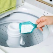 Powdered laundry detergent being added to top load washer