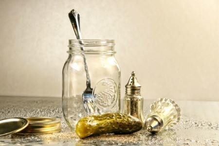 Pickle and old fashioned salt and pepper shakers next to an empty jar with a fork in it.