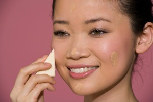 Woman applying foundation to skin with a make-up sponge
