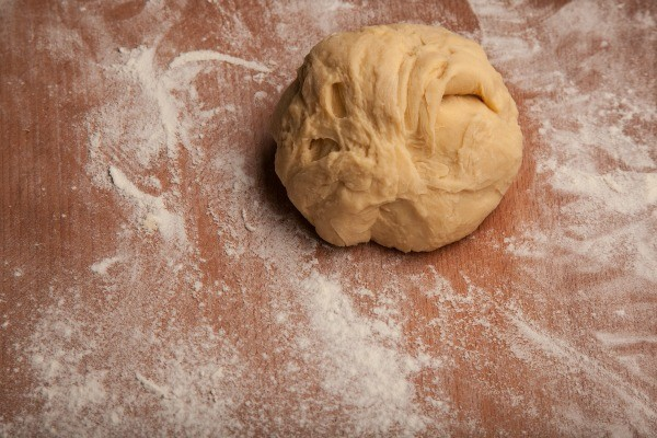 Ball of pizza dough on flour dusted work surface