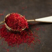 Measuring spoon spilling over with saffron threads