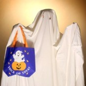 Child dressed as a ghost holding a bag labelled Trick-Or-Treat!