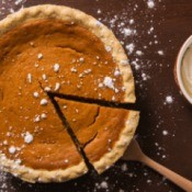 Photo of a pumpkin pie with small cracks in it and one slice being taken out.