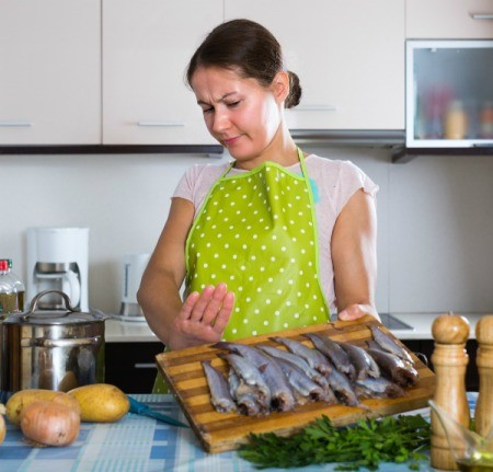 Woman with several fish on a cutting board pushing them away because they smell
