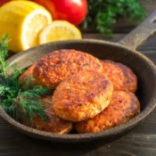 Salmon cakes in a cast iron pan with a sprig of dill.