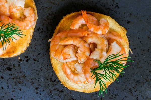 Shrimp on a round slice of toast.