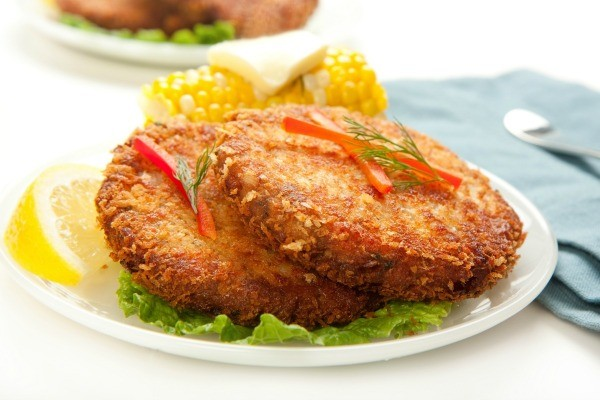 2 Fried salmon patties with a wedge of lime and a cob of corn.