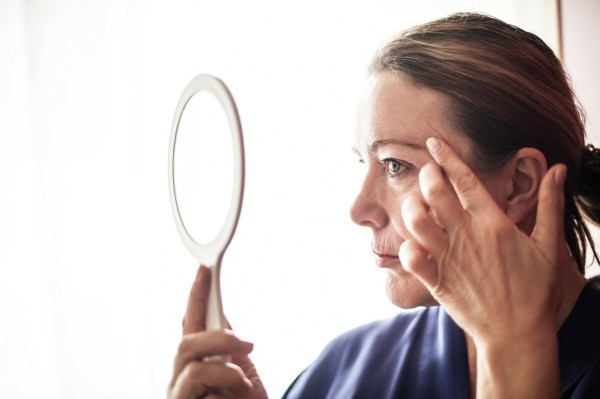 A woman looking at her face in a mirror.