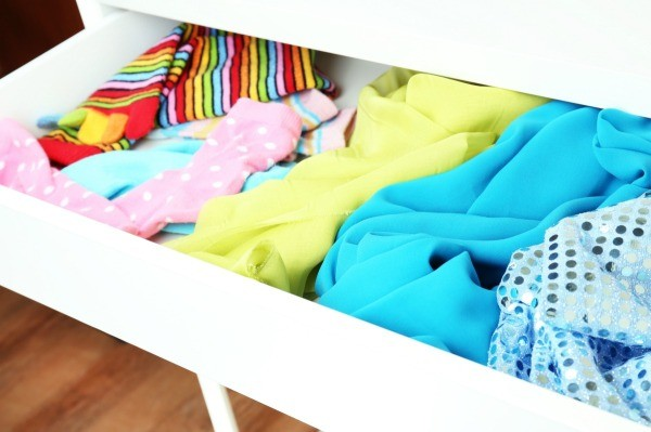 Clothes in a white dresser drawer.