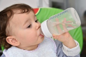 Infant drinking water from a bottle
