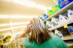 Back of a woman scratching her head in confusion at the laundry detergent aisle of the super market