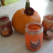 Three of the glass bottle candle holders arranged around a pumpkin.