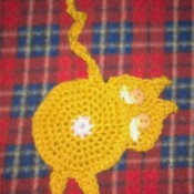 Crochet coaster of a cat looking back over its shoulder.