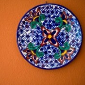 Decorative plate hanging on an orange wall.