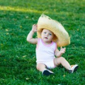A baby wearing a overly large straw hat.