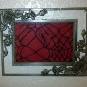 Spiderweb lace inside a silver filigree frame.