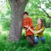 Boy and girl laughing and playing next to a tree trunk surrounded by tall weed-type grass