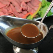 A ladle of au' jus served with roast beef.