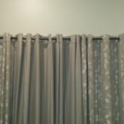 Grayish taupe curtains hanging against a neutral colored wall.