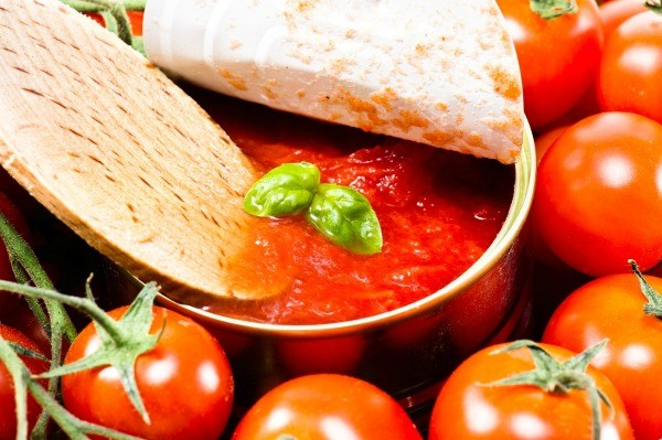 Wooden spoon dipping into can of tomato soup with basil.  Can is surrounded by tomatoes
