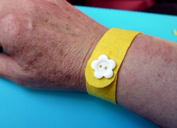 yellow felt wristband with white flower button on woman's wrist