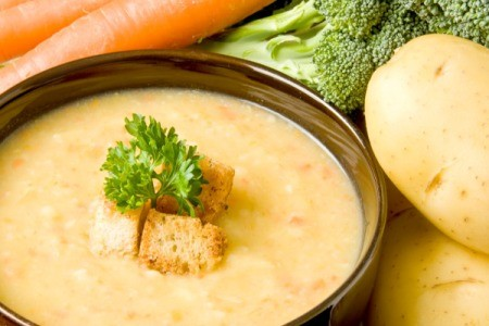 A bowl of a hearty potato soup made with many vegetables.