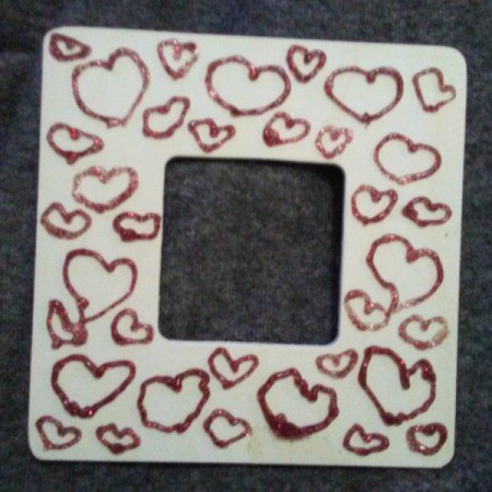 A wooden frame with red glitter hearts.