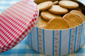 A cookie tin filled with cookies.