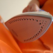A clothes iron taking wrinkles out of orange fabric.