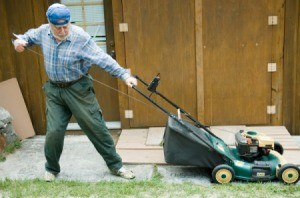 A man pulling on a cord to start a lawnmower.