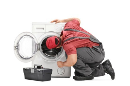 A repairman looking at a washing machine.