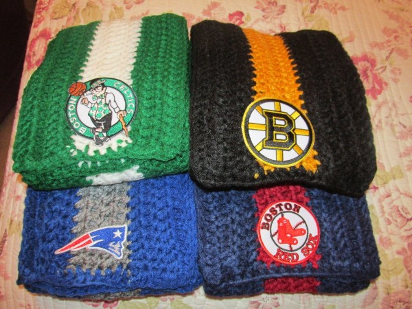 four crocheted team scarves