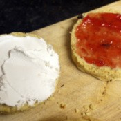 A scone with cream on one side and jelly on the other.