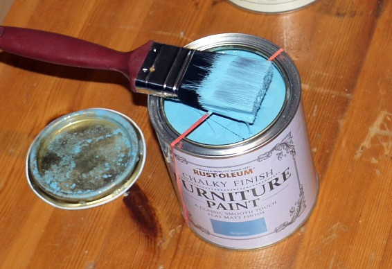 An elastic band stretched across the paint can opening.