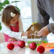 A toddler and her dad making a gingerbread house.